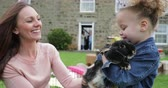 orelhas : Little girl excited while stroking a pet rabbit ourdoors at a easter garden party.