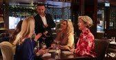 waiter : Male waiter recommending a bottle of champagne to a small group of female friends in a restaurant. Stock Footage