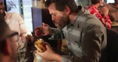chignon : Mid adult man sitting in a restaurant with his friends. He takes a big bite out of his burger and showing his enjoyment.