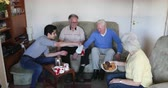 social worker : Teenage boy is assisting senior adults having a tea party at a nursing home. Stock Footage