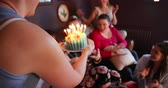 выпивка : Tracking shot of a unrecognisable female woman carrying a birthday cake. A small group of female friends arecelebrating a birthday with a Birthday cake while relaxing at home.