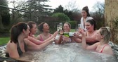 egész : Small group of female friends socialising and relaxing in the hot tub on a weekend away. They are celebrating with a glass of champagne. Stock mozgókép
