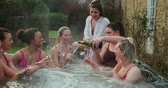 inteiro : Small group of female friends socialising and relaxing in the hot tub on a weekend away. They are celebrating with a glass of champagne. Stock Footage