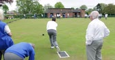 A rear view shot of a senior man taking his shot in a game of lawn bowling. 動画素材