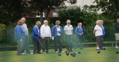 A side-view panning shot of a group of senior friends lawn bowling on grass.
