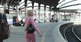 A businesswoman walking down a platform in a train station with a businessman closely following behind. The woman is talking through her headphones to someone on the other end of her phone. She eventu