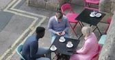jorkšírský : Two businessmen and a businesswoman sitting at an outdoor table in a city having a hot drink while discussing work and looking at mobile phones. Dostupné videozáznamy