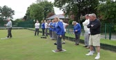 организованный : A side-view panning shot of a group of senior friends lawn bowling on grass, one senior woman takes her shot.