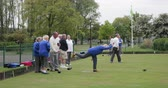 A side-view panning shot of a group of senior friends lawn bowling on grass, one senior woman takes her shot.