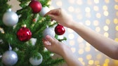 close up of woman putting ornament on Christmas tree