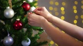 Christmas tree decoration - woman putting ornament on Christmas tree in decorated room Стоковые видеозаписи