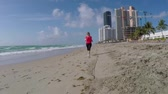 jogging yapan : Girl Runs on Sunny Isles Beach Miami tracking shot