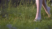 bare forest : Barefoot Young Woman Walk on Green Grass in forest. From left to right