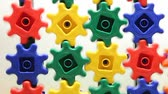 mecanismo : colorful plastic gears turning on a white background