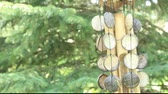 тон : bamboo and shell wind chime blowing in the breeze