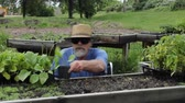 disabled man in a wheelchair working at a potting bench Wideo