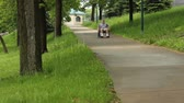 man in a wheelchair rolling down a steep sidewalk Stock Footage