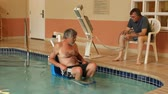 mature handicapped man being extracted from a pool with a lift