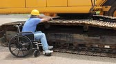 disabled maintenance mechanic working on the tracks of a large backhoe