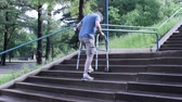 mature man using a walker to ascent a set of steps