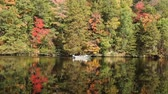 A small fishing boat floating on an Autumn river Wideo