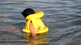 безопасный : Little boy in orange life vest swimming in wave sea (selective DOF)