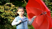 chilly : handsome cute boy with brown eyes in a jeans jacket in the autumn park with a red umbrella, Stock Footage
