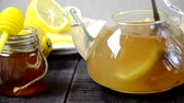 гомеопатический : put turmeric honey hot water in a teapot to make a healthy drink. Teapot of ginger tea with honey and lemon on wooden table. Cup of ginger tea with honey and lemon on wooden table