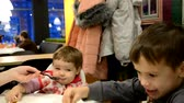 four children : Family Enjoying Snack In Cafe Together. brother and sister play together during lunch or dinner