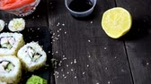 меню : Eating Sushi with chopsticks. Sushi roll japanese food in restaurant. California Sushi roll set with salmon, vegetables, flying fish roe and caviar closeup. Japan restaurant menu