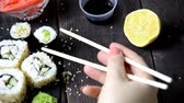 унаги : Eating Sushi with chopsticks. Sushi roll japanese food in restaurant. California Sushi roll set with salmon, vegetables, flying fish roe and caviar closeup. Japan restaurant menu