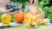 woman makes Infused detox water with blueberry, orange and mint. in glass mason jar against a background of green foliage. of health, diet, weight loss, cleansing of toxins, cut fruits by the knife