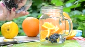 mirtilos : woman makes Infused detox water with blueberry, orange and mint. in glass mason jar against a background of green foliage. of health, diet, weight loss, cleansing of toxins, cut fruits by the knife