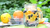 no idea : woman makes Infused detox water with blueberry, orange and mint. in glass mason jar against a background of green foliage. of health, diet, weight loss, cleansing of toxins, cut fruits by the knife
