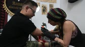 perfurante : KRAKOW POLAND  JUNE 6 2015: People make a tattoos at the 10th International Tattoo Convention in the CongressEXPO Center. This year anniversary TattooFest is tattoo Studio with an area of 2000m2.