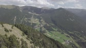 Aerial footage of the green Pyrenean mountains in the summer. Drone flies over the green mountains in La Massana, Andorra. There are brown buildings and winding roads in the distance. Stock mozgókép
