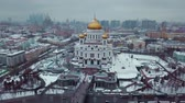 The drone flies around russian Orthodox Cathedral of Christ the Savior in Moscow in winter. In the shot also Moscow City, Soviet skyscrapers, historic buildings, churches, driving cars. It is cloudy and snowing outside. Stock mozgókép
