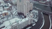 Drone flies over the Moscow River and the road with cars and flies up to the Stalinist skyscraper (USSR). It is winter and snow everywhere.