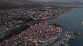 Drone flies over medieval town Trogir, historical center, above churches, old architecture, port and boats. Summer.