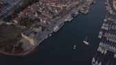 Aerial footage of Trogir port in Croatia at sunset. White boats standing and floating on the sea.