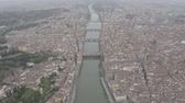Aerial view of Ponte Vecchio bridge on Arno river in Florence city historical center, Italy. Italian orange roofs from drone near Cathedral. Tuscany. LOG.