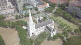 끝 : Aerial view Gothic Church in Singapore, green grass, trees and high buildings near the church. 무비클립