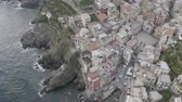 rocky mountains : Aerial view of Riomaggiore Bay village. Colorful italian houses on rocky coast. Boats floating in the sea. Foaming waves breaking on stones. Cinque Terre, Italy.