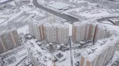 administrativo : Aerial footage of residential complex, sleeping area in winter. Modern large panel houses, high buildings, kinder yards, sport ground and highway with going cars. Cars paarked near houses. Novo-Peredelkino, Moscow, Russia.