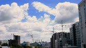 Tower cranes on a background of clouds in the city