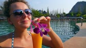 travel : Girl Drinking Fresh Mango Juice in Luxury Pool on Vacation. Slow Motion. HD, 1920x1080.