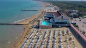 зонтик : LIGNANO, ITALY - MAY, 2019: Lignano beach at Adriatic sea coastline in Italy aerial drone view. Europe during summer.