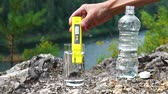 измерительный : Man makes measurement of PH in glass of clean water on mountain area. Theme of health and ecology. Slowmotion Стоковые видеозаписи