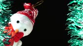 kardan adam : Cute snowman in red hat and bow looks at you from scene. Christmas greeting on black background. Festive mood. New Year or holiday theme Stok Video