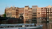Tourist boat in Amsterdam canal and Church of Saint Nicholas on